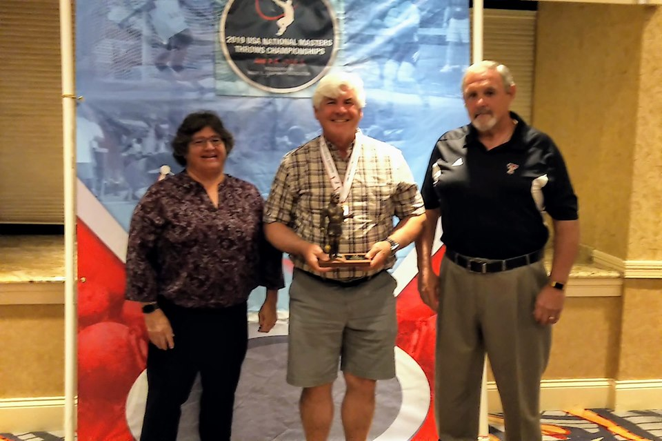 Jim Burgoyne, center, President of the Twilight Throwers, won the Ken Weinbel Award for Contributions to the Masters Throwing Community — with Throwing Events Subcommittee Chair Sue Hallen (left) and fellow Twilight Thrower Bob Cedrone (right).